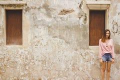 Vrouw die zich met oude muur bevinden stock foto