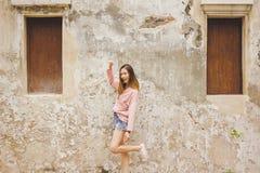 Vrouw die zich met oude muur bevinden royalty-vrije stock fotografie