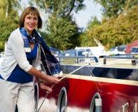 Vrouw die zich naast een boot bevinden Stock Foto's