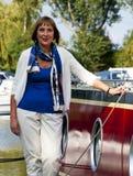 Vrouw die zich naast een boot bevinden Stock Afbeelding