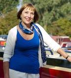 Vrouw die zich naast een boot bevinden Stock Afbeeldingen