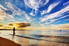 Vrouw die zich in oceaan bevinden. Dramatische zonsonderganghemel Royalty-vrije Stock Foto's
