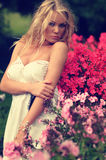 Vrouw die zich onder Bloemen bevindt stock fotografie