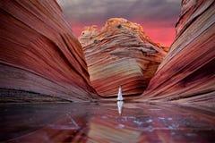 Vrouw die zich op bevroren meer met kleurrijke rotsen bij zonsopgang bevinden stock afbeelding