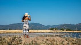 Vrouw die zich op de hoed van de heuvelholding bevinden en dorp in dis bekijken stock fotografie