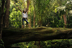 Vrouw die zich op een gevallen boom bevindt stock fotografie