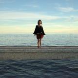 Vrouw die zich op een pier in het recente middaglicht bevinden royalty-vrije illustratie