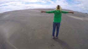 Vrouw die zich op een zandduin tegen sterke wind bevinden stock video