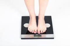 Vrouw die zich op gewichtsschalen bevinden Stock Afbeeldingen