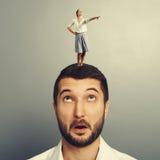 Vrouw die zich op het hoofd van de verbaasde mens bevinden Stock Afbeeldingen