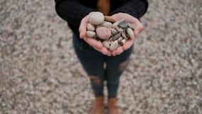 Vrouw die zich op kust van de stenen van de meerholding in vorm van hart bevinden stock videobeelden