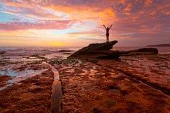 Vrouw die zich op kustrotsen met overweldigende zonsopgang en bezinningen bevinden royalty-vrije stock fotografie