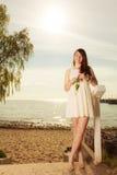 Vrouw die zich op strand bevinden die roze tulp houden royalty-vrije stock fotografie