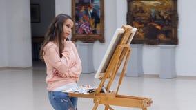 Vrouw die zich voor canvas bevinden die geconcentreerd kijken stock footage