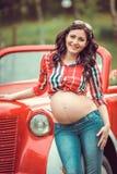 Vrouw die zich voor retro rode auto bevinden Stock Afbeelding