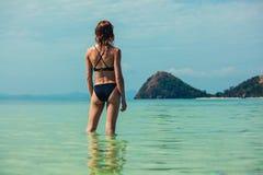 Vrouw die zich in water door tropisch strand bevinden Stock Afbeelding