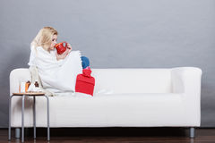 Vrouw die ziek hebbend griep die op bank liggen zijn royalty-vrije stock foto