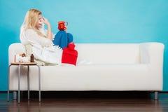 Vrouw die ziek hebbend griep die op bank liggen zijn Stock Foto's