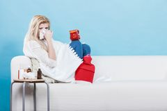 Vrouw die ziek hebbend griep die op bank liggen zijn Royalty-vrije Stock Foto's
