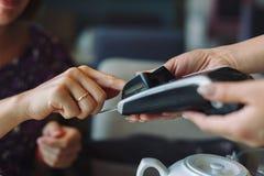Vrouw die zijn rekening in restaurant betalen stock foto's