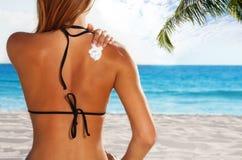 Vrouw die zonbescherming op gelooide rug toepassen royalty-vrije stock afbeelding