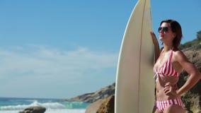 Vrouw die zonnebril met een in hand surfplank dragen stock footage
