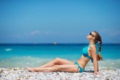 Vrouw die in zonnebril van zonneschijn op strand geniet Royalty-vrije Stock Foto