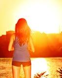 Vrouw die zonsondergang van zonneschijn na het lopen genieten Royalty-vrije Stock Foto's