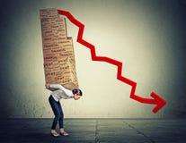 Vrouw die zwaar dozenhoogtepunt van financiële schuld dragen die langs grijze muurachtergrond lopen Stock Foto