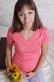 Vrouw die zwangere buik in slaapkamer houden Stock Afbeeldingen