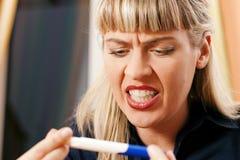 Vrouw die zwangerschapstest doet die ongelukkig is Royalty-vrije Stock Afbeeldingen