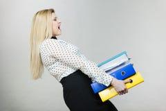 Vrouw die zware kleurrijke bindmiddelen met documenten houden Stock Afbeelding