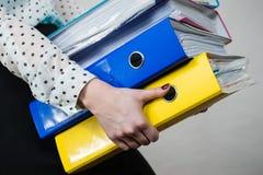 Vrouw die zware kleurrijke bindmiddelen met documenten houden Royalty-vrije Stock Afbeeldingen