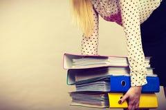 Vrouw die zware kleurrijke bindmiddelen met documenten houden Stock Foto's