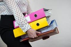 Vrouw die zware kleurrijke bindmiddelen met documenten houden Stock Afbeeldingen