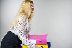 Vrouw die zware kleurrijke bindmiddelen met documenten houden Royalty-vrije Stock Foto's