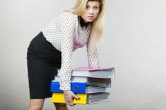 Vrouw die zware kleurrijke bindmiddelen met documenten houden Royalty-vrije Stock Fotografie
