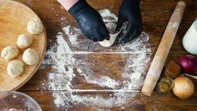 Vrouw die in zwarte handschoenen gehakt toevoegen aan deeg voor het maken van pastei met vlees of khinkali stock videobeelden