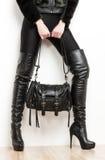 Vrouw die zwarte kleren en laarzen draagt Stock Foto's