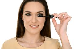 Vrouw die zwarte mascara op wimpers met make-upborstel toepassen stock foto's