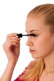 Vrouw die zwarte mascara op wimpers toepassen, die make-up doen Stock Foto