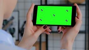 Vrouw die zwarte smartphone met het lege groene scherm houden - chroma zeer belangrijk concept stock footage