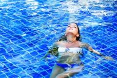 Vrouw die in zwembad drijven Royalty-vrije Stock Afbeeldingen