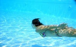 Vrouw die in zwembad met bezinningen duikt royalty-vrije stock foto