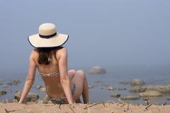 Vrouw die zwemmend kostuum met de halve zitting van de strohoed op zandzon dragen die en aan het overzees in mist baden kijken Stock Foto's