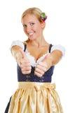 Vrouw in dirndl die twee duimen tegenhouden Stock Fotografie