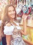 Vrouw in Dirndl-kostuum met Peperkoekhart Stock Foto's