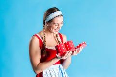 Vrouw in dirndlkleding het openen gift - of heden Stock Foto