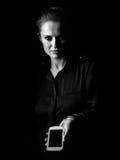 Vrouw in donkere kleding die op zwarte het tonen smartphone wordt geïsoleerd Stock Afbeelding