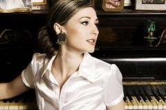 Vrouw door de piano Stock Afbeeldingen